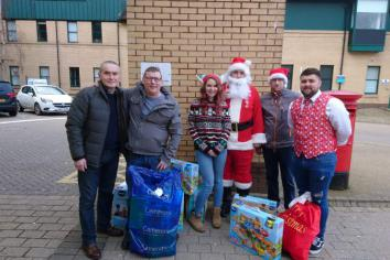 Former Wrightbus workers hand over Christmas toy parcels to children in hospital